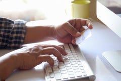 拿着网上购物的男性手播种的射击信用卡在书桌 图库摄影