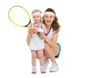 拿着网球拍的愉快的母亲和婴孩画象  免版税图库摄影