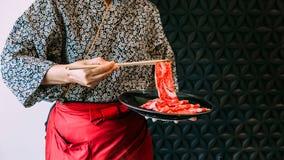 拿着罕见的切片Wagyu A5牛肉的妇女佩带的和服由煮沸的筷子在Sukiyaki火锅 免版税库存照片
