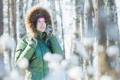 拿着羊毛制手套的年轻可爱的妇女在冬天森林里临近她的头户外 免版税库存图片