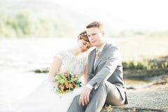 拿着美丽的婚礼花束的新娘和新郎 摆在河附近 库存照片