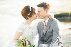 拿着美丽的婚礼花束的新娘和新郎 摆在河附近 免版税库存图片