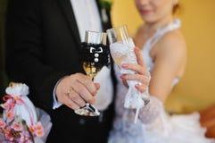 拿着美丽的婚礼香槟玻璃的新娘和新郎 免版税图库摄影