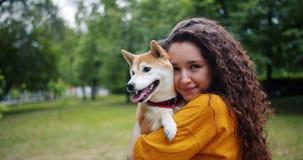 拿着美丽的小狗的愉快的年轻女人画象在公园在夏天 股票录像