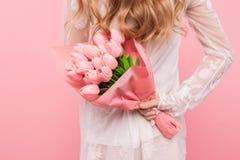 拿着美丽的桃红色郁金香的花束妇女,在桃红色背景,情人节,国际妇女节概念 库存图片