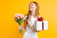 拿着美丽的花和一个礼物盒的花束愉快的女孩在黄色背景 免版税库存照片