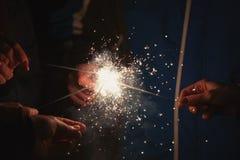 拿着美丽的闪烁发光物的朋友为庆祝新年 库存图片