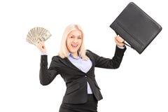 拿着美元和公文包的一名愉快的女实业家 免版税库存图片