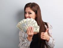 拿着美元和显示赞许si的愉快的年轻偶然妇女 免版税库存图片