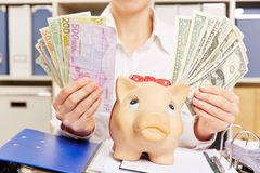 拿着美元和欧元接近存钱罐的手 库存图片