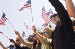 拿着美国国旗的人们在集会期间 免版税库存照片