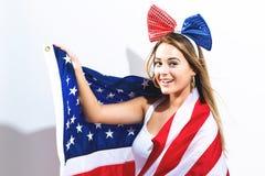 拿着美国国旗的愉快的少妇 库存照片
