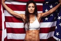 拿着美国国旗的肌肉少妇 库存图片