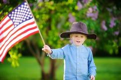 拿着美国国旗的逗人喜爱的小孩男孩在美丽的公园 图库摄影