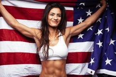 拿着美国国旗的年轻女运动员 免版税图库摄影