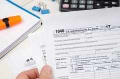 拿着美国报税表的人1040 免版税库存图片