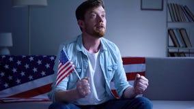 拿着美国旗子和观看在电视家的情感美国人选举结果 库存图片