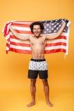 拿着美国旗子的一个愉快的激动的非洲人的画象 免版税库存照片