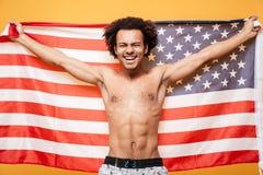 拿着美国旗子的一个赤裸上身的美国黑人的人的画象 图库摄影