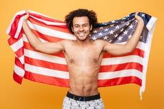 拿着美国旗子的一个赤裸上身的美国黑人的人的画象 免版税库存图片