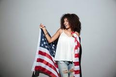 拿着美国旗子的愉快的爱国的非洲妇女 图库摄影