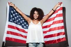 拿着美国旗子的愉快的爱国的非洲妇女 库存照片
