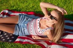 拿着美国旗子的年轻愉快的爱国者妇女 免版税库存图片
