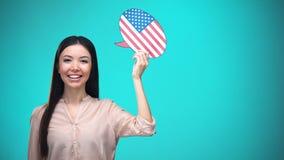 拿着美国旗子讲话泡影的微笑的女孩,学会语言,旅行想法 影视素材