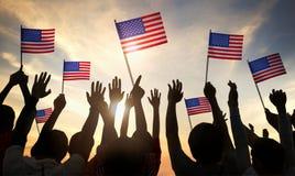 拿着美国的旗子的人剪影  免版税库存照片