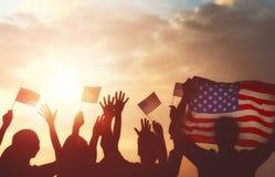 拿着美国的旗子的人们 免版税库存图片