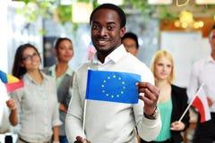 拿着美国的旗子的愉快的非洲商人 库存照片