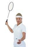 拿着羽毛球拍的女运动员准备服务 库存照片