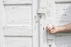 拿着老土气双门的门把手一个人的手 免版税库存图片