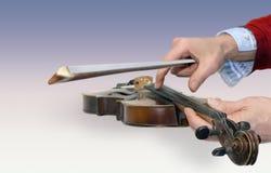 拿着老小提琴和弓的人的手 免版税库存照片