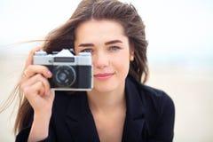 拿着老影片照相机的美丽的女孩 库存照片
