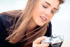 拿着老影片照相机的美丽的女孩 免版税库存图片