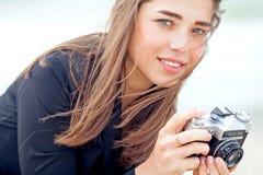 拿着老影片照相机的美丽的女孩 免版税库存照片