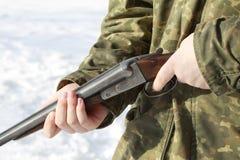 拿着老猎枪的猎人的特写镜头在冬天森林里 免版税库存照片