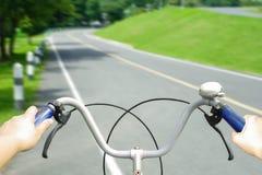 拿着老自行车的把手在柏油路的游人的手 免版税图库摄影