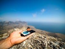 拿着老葡萄酒指南针的旅客在被弄脏的山和海的晴天 库存照片
