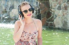 拿着耳机和听到音乐的夫人外面 库存图片