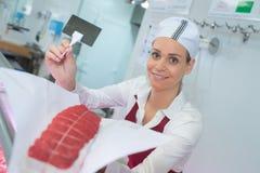 拿着联合牛肉和空白的标签的女性屠户 免版税库存图片