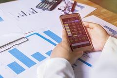 拿着股市的巧妙的电话和检查投资 有在桌上的一张计划图 免版税库存图片