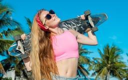 拿着肩膀的少妇画象长的委员会在海滩的棕榈附近 免版税库存图片