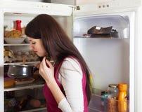 拿着肮脏的食物的Brunnette妇女在冰箱附近 免版税库存照片