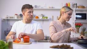 拿着胡椒切片的滑稽的人作为玻璃,获得与妻子的乐趣在厨房 股票录像