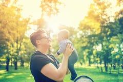拿着胳膊的年轻爸爸精美新生儿室外在公园 愉快的育儿概念、父亲节和家庭 免版税库存照片