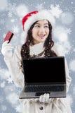 拿着膝上型计算机和信用卡的冬天外套的妇女 免版税库存图片