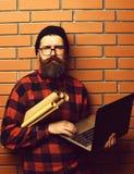 拿着膝上型计算机和工艺纸的有胡子的残酷白种人行家 免版税图库摄影