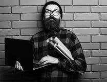 拿着膝上型计算机和工艺纸的有胡子的残酷白种人行家 免版税库存照片